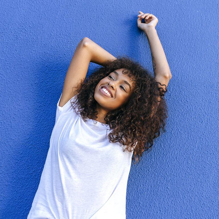 دختری با تی شرت سفید کنار دیوار آبی